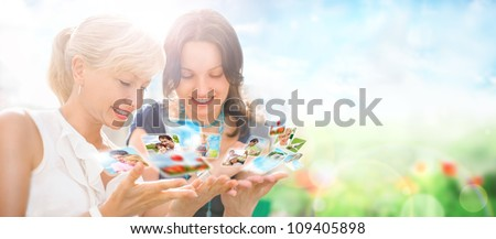 Portrait of two happy women mother and daughter looking their photo and video files in social media resources using virtual interface of future. Outdoors at beautiful idyllic place. - stock photo
