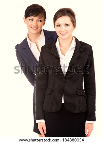 Portrait of two happy young business women standing and smiling, white background - stock photo