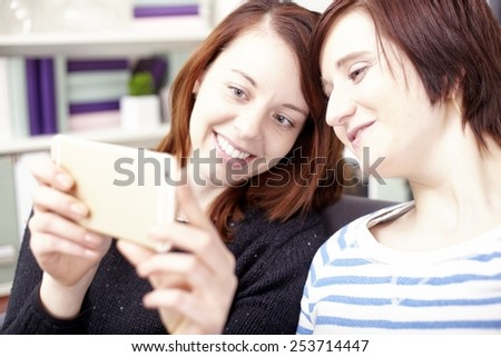portrait of two happy young girls with smart phone at home
