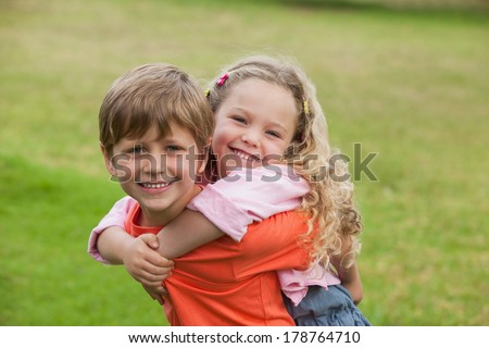 Portrait of two happy young kids playing at the park - stock photo