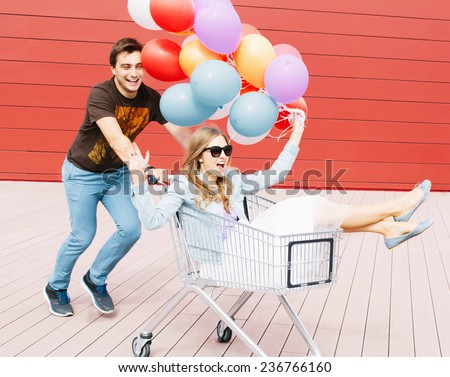 Portrait of two happy young people dating and having fun. Girl sitting in shopping cart and keeping color balloons in hand. Guy rolling trolley. Red background. Outdoors - stock photo