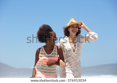 Portrait of two happy young women walking at the beach together