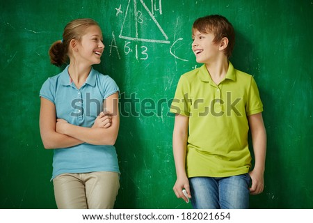Portrait of two joyful classmates looking at one another by the blackboard - stock photo