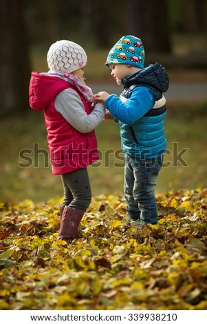 Portrait of two kids in the park as they talk together - stock photo