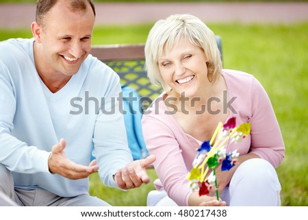Portrait of two laughing mature people with pinwheel