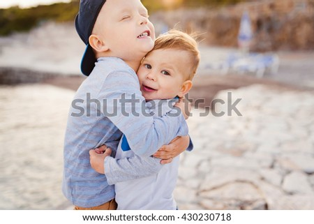 Portrait of two little boys brothers hugging each other outside. Sibling sentiment - stock photo
