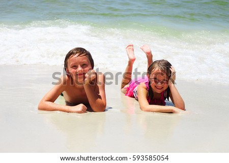 Portrait of two little children lying on sand at water edge, looking at camera and smiling. Siblings or friends resting at summer resort