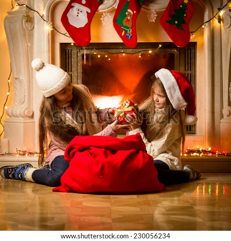 Portrait of two little girls having a fight of present on Christmas - stock photo