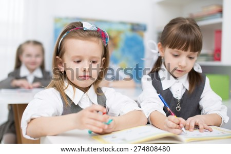 Portrait of two little girls looking at camera at workplace with children on background - stock photo