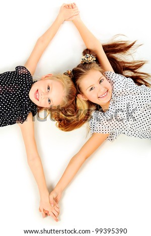 Portrait of two little girls sisters posing at studio. Isolated over white. - stock photo