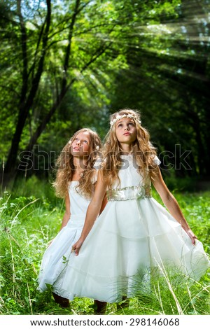Portrait of two little princesses wearing white dresses in forest. - stock photo