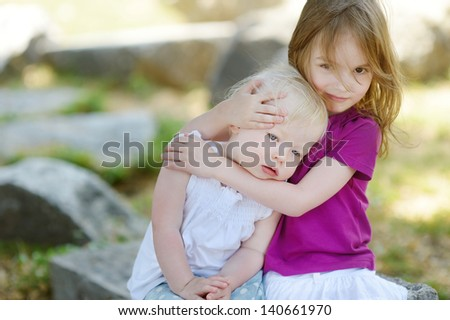 Portrait of two little sisters outdoors - stock photo