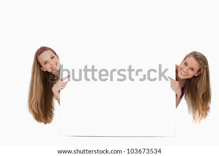 Portrait of two long hair women back of a blank sign against white background - stock photo