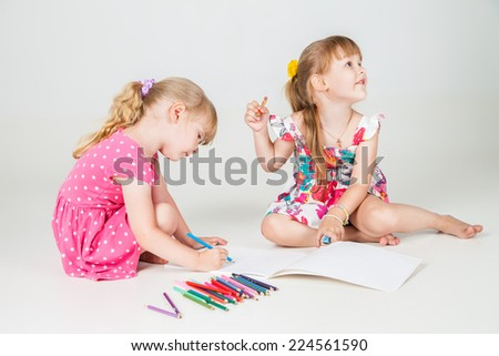 Portrait of  two lovely girls drawing with colorful pencils - stock photo