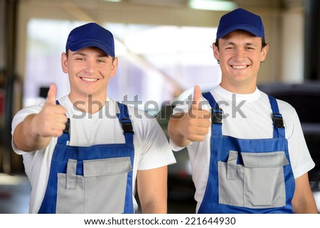 Portrait of two male mechanics in auto repair service - stock photo