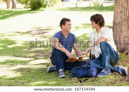 Portrait of two male students talking in a park - stock photo