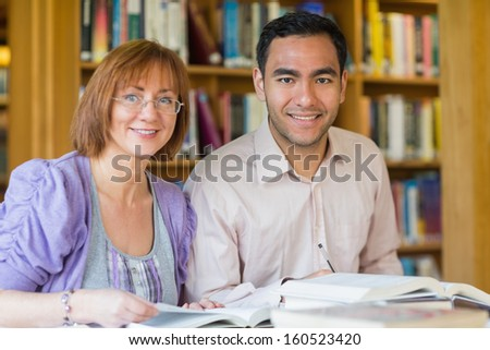 Portrait of two mature students studying together in the library