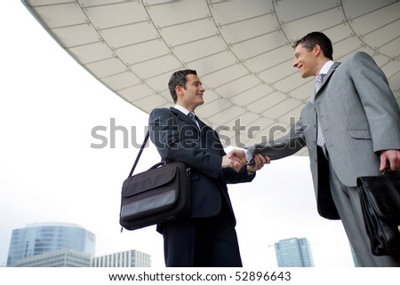 Portrait of two men shaking hands - stock photo