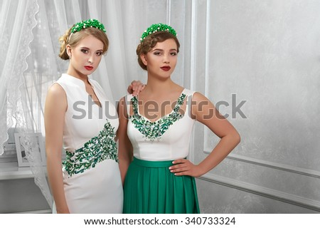 portrait of two models, brunette, smiling blonde in white dress and green dress, hands on hips, in a room on the background of window. - stock photo