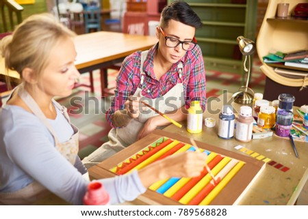 Portrait of two modern female artists enjoying  working together in art studio painting together sitting at wooden desk