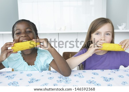 Portrait of two multiethnic girls eating corn cobs at table - stock photo