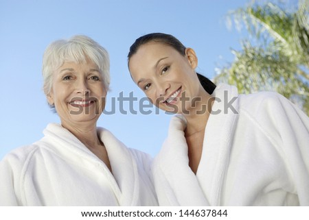 Portrait of two multiethnic women in bathrobes against blue sky at spa - stock photo