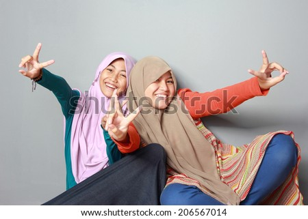 portrait of two muslim sister having fun together on grey background