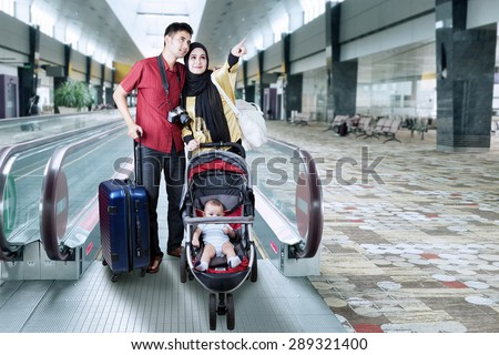 Portrait of two parents holiday together with their baby on the pram and standing in the airport hall - stock photo