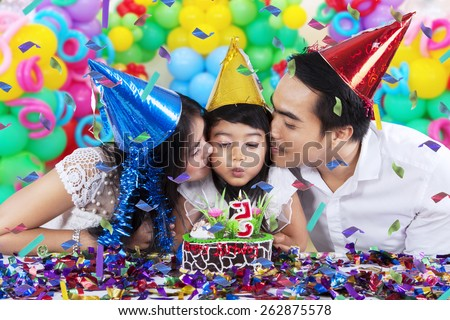 Portrait of two parents kissing their daughter while blowing a birthday candle at home - stock photo