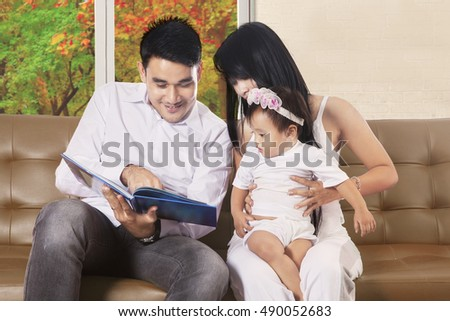 Portrait of two parents sitting on sofa and read book with their daughter, autumn on the window