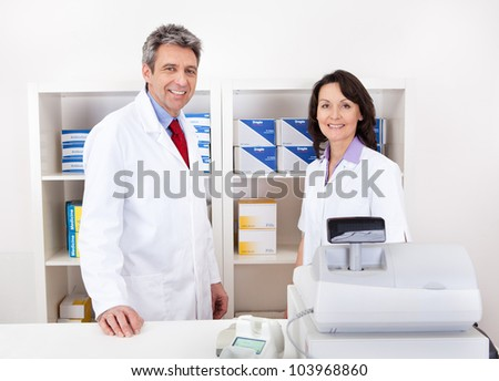Portrait of two pharmacists at the drugstore smiling - stock photo