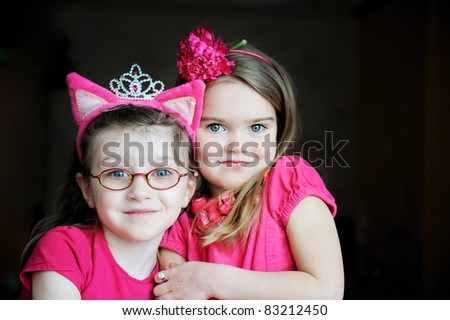 Portrait of two pinky child girls on black background - stock photo