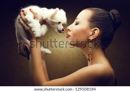 Portrait of two playing friends: fashionable model with sexy red lips holding her white little chinese crested dog. Both posing over golden background. Studio shot - stock photo