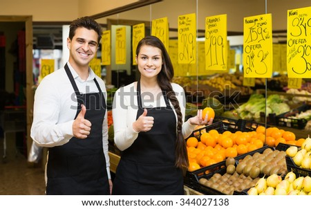 Portrait of two positive european workers with seasonal fruits, prices on Spanish