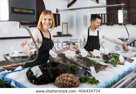 Portrait of two positive smiling sellers working at the counter in fish store - stock photo