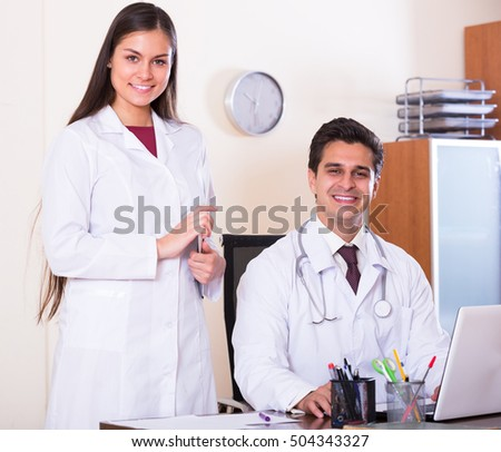Portrait of two positive therapeutists with stethoscope in private clinic