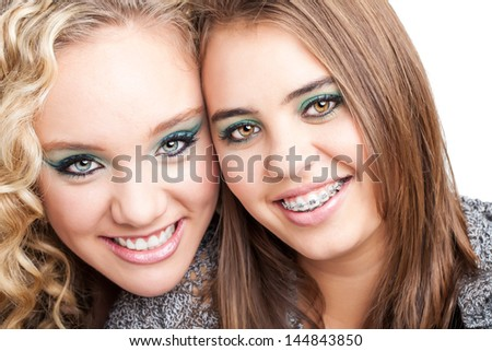 portrait of two pretty caucasian friends smiling brightly and one friend showing off braces - stock photo