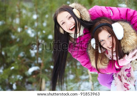 Portrait of two pretty girls in winter park having fun - stock photo