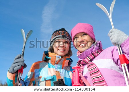 Portrait of two pretty girls with mount  skis against blue sky - stock photo