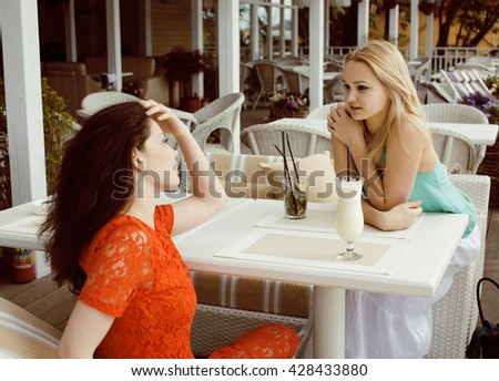 portrait of two pretty modern girl friends in cafe open air interior drinking and talking, having chat and coctail, lifestyle friendship concept - stock photo