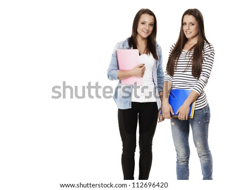 portrait of two pretty student teenagers with note pads on white background - stock photo