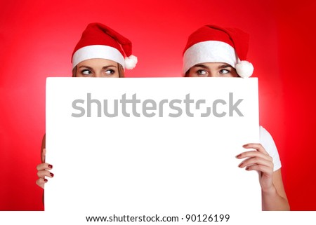 Portrait of two pretty women with Christmas hats holding poster on a red background