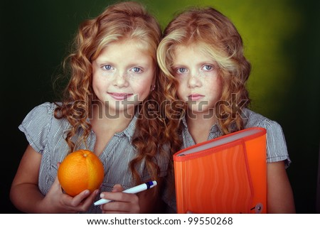 Portrait of two red hair sisters holding orange stuff - stock photo