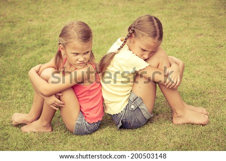 Portrait of two sad sister sitting on the grass at the day time - stock photo