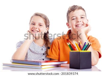 Portrait of two school kids at the desk, isolated on white background - stock photo