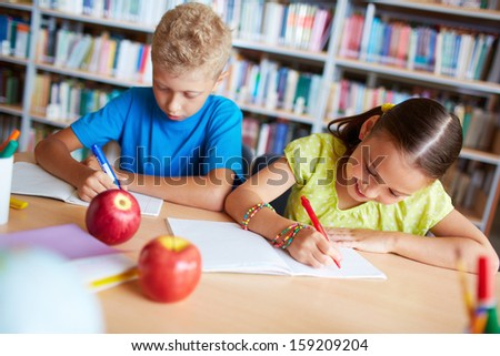 Portrait of two schoolkids sitting in library and making notes - stock photo