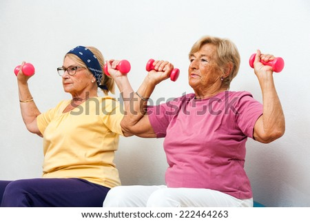 Portrait of two Senior female fitness girls exercising muscles with weights in gym.