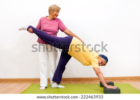 Portrait of two Senior ladies helping each other with stretching exercise in gym.