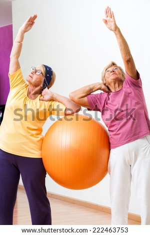 Portrait of Two Senior women stretching with gym ball in health club.