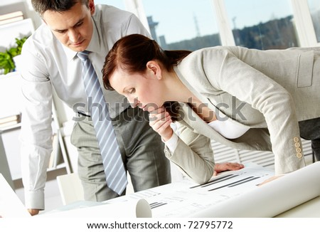 Portrait of two serious architects looking at document in office